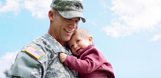 veteran in uniform holding a small boy in his arms