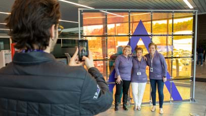 Office co-workers taking a photo In front of a purple uplift symbol